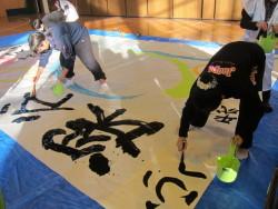 大きな紙に文字を描く参加者