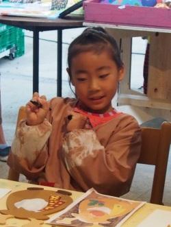 トナカイをかたどった板に色を塗る女の子