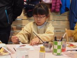 トナカイをかたどった板に色を塗る女の子2