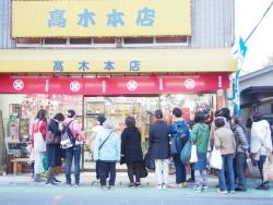ひな人形店の前で若女将から説明を受ける参加者